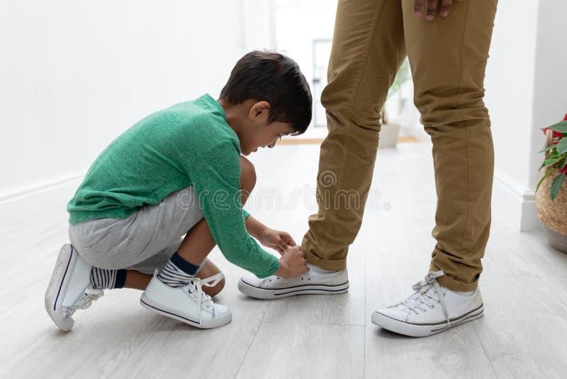 在家栓他的父亲鞋带的男孩 免版税库存照片