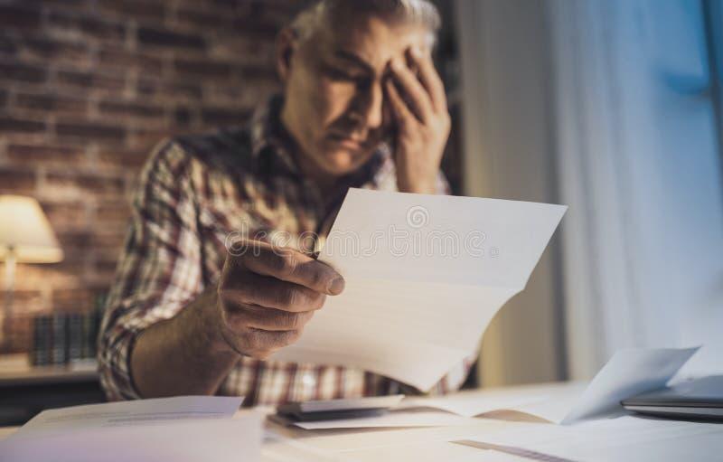 在家检查他的国内汇票的绝望人 免版税库存照片