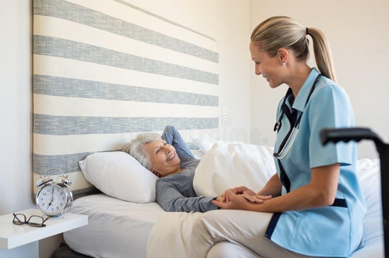 在家检查资深妇女的护士 免版税库存照片