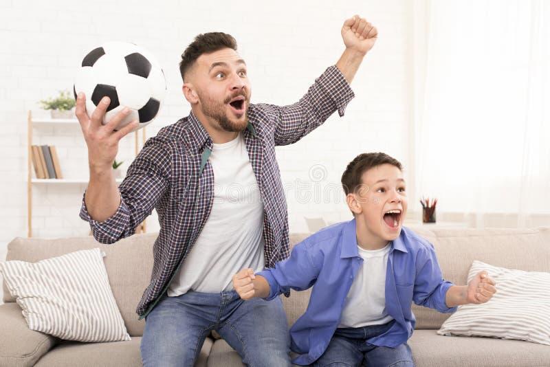 父亲和儿子欢呼与橄榄球球的足球迷 免版税库存照片