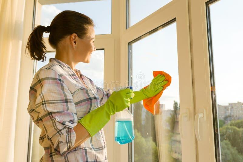 在家洗涤与橡胶防护手套的成熟妇女窗口与喷雾器洗涤剂和microfiber旧布 免版税库存照片