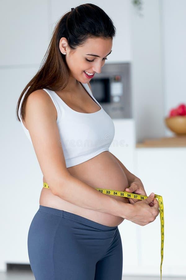 在家测量她的有磁带的美丽的年轻孕妇腹部 免版税图库摄影