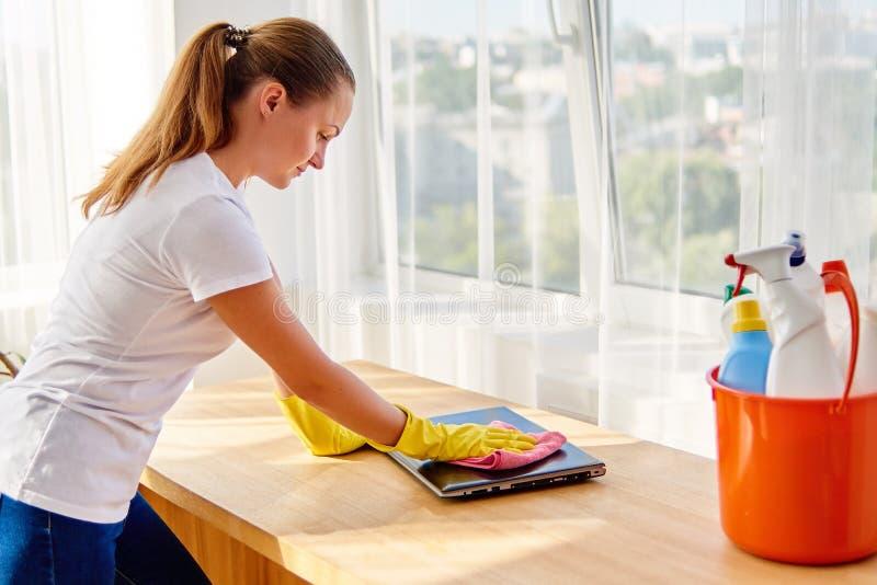 在家清洗和抹尘土的白色衬衫和黄色防护橡胶手套的妇女与在手提电脑的桃红色旧布 图库摄影