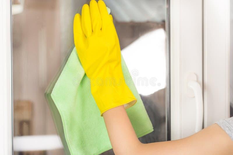 在家清洗窗口的年轻女性手与绿色旧布和防护黄色手套 免版税库存图片