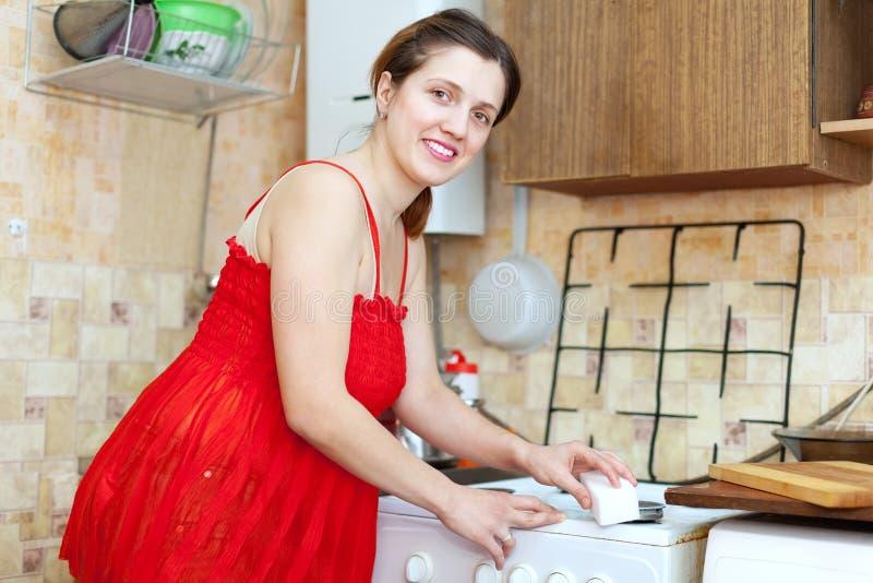 清洗气体火炉的红色的主妇与海绵 库存图片
