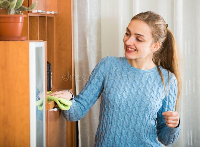 在家清洗蓝色的球衣的快乐的女孩 库存照片