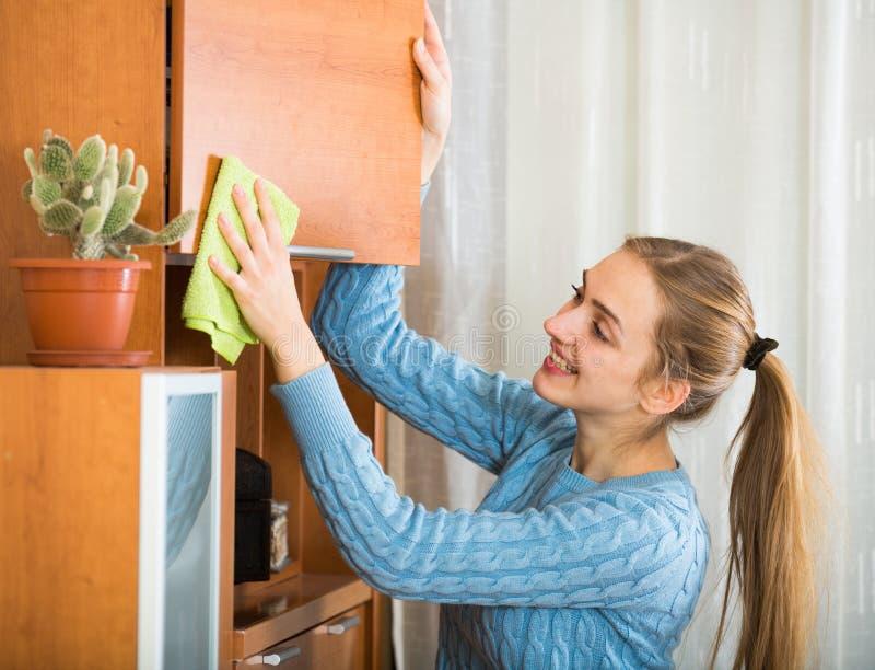 在家清洗蓝色的球衣的快乐的女孩 免版税库存照片