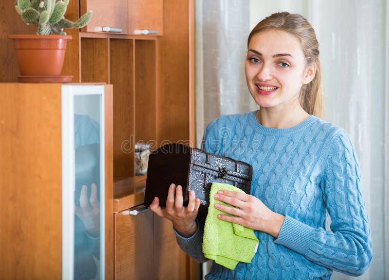在家清洗蓝色的球衣的快乐的女孩 免版税库存图片