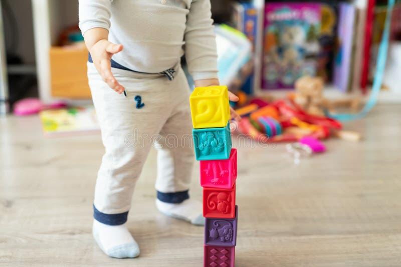 在家演奏五颜六色的玩具的逗人喜爱的可爱的白种人男婴 有愉快的孩子软的橡胶立方体乐趣修造的塔  免版税图库摄影