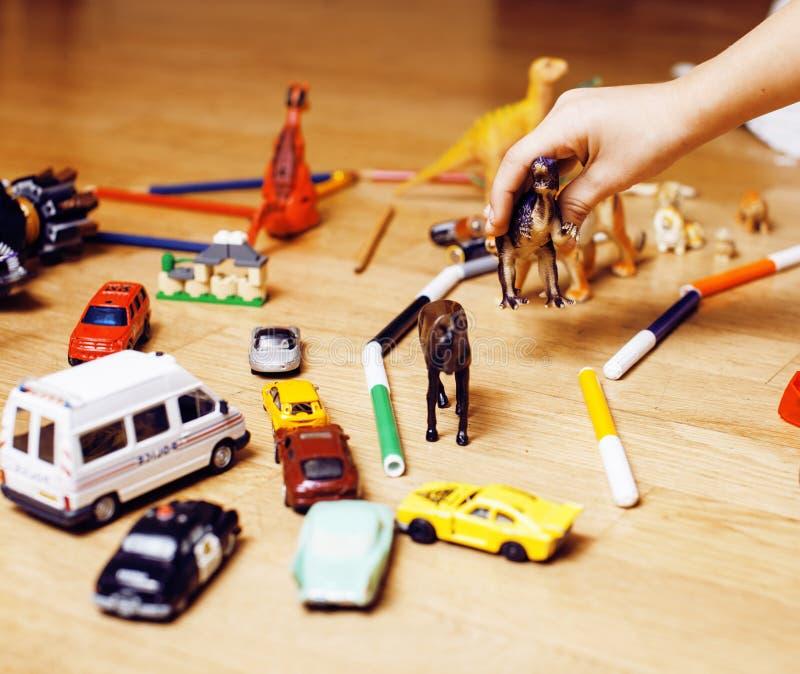 在家演奏在地板上的孩子玩具,在混乱,自由教育的一点手 库存照片