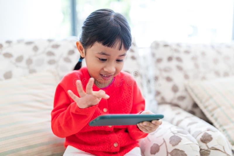 在家演奏手机的小女孩 免版税图库摄影