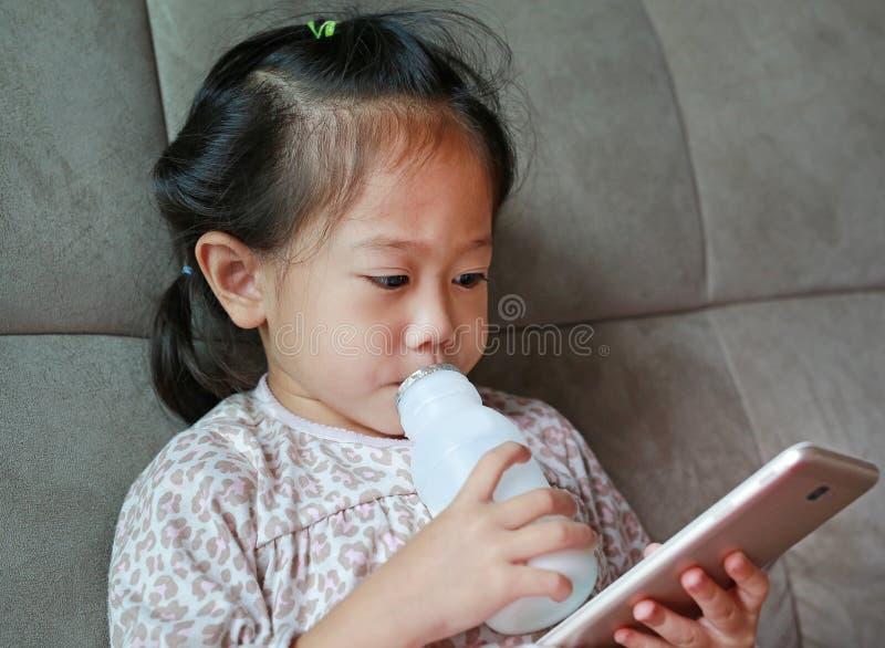 在家演奏智能手机和饮用奶与秸杆的可爱的小孩女孩在灰色沙发 免版税图库摄影