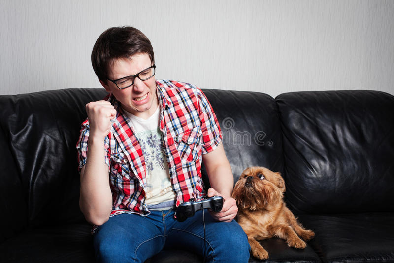 在家演奏比赛playthrough或初排录影的年轻人 可爱的人佩带镜片 他是愉快赢取这棵无花果 免版税库存照片