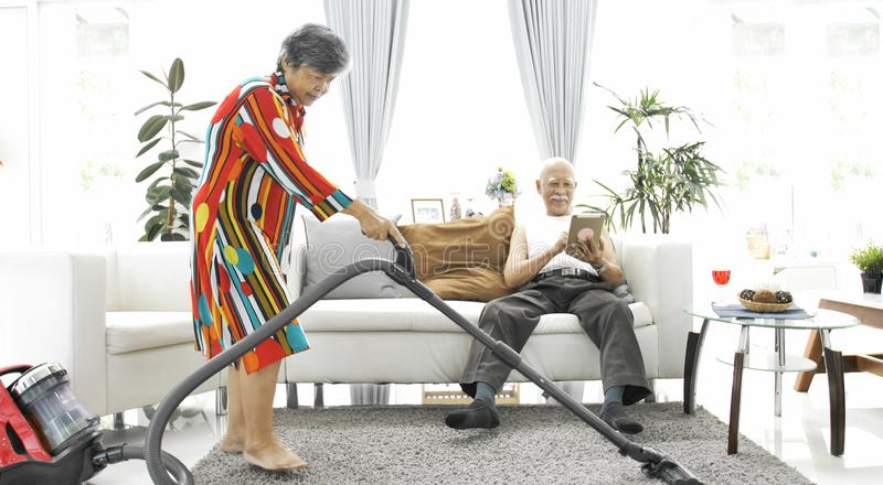 在家演奏片剂计算机和资深妇女吸尘的地板的愉快的亚裔老人 库存图片