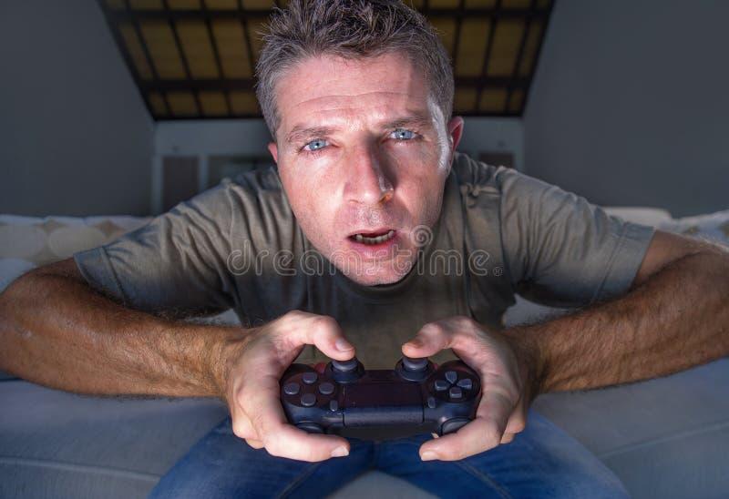 在家演奏电子游戏客厅的年轻人被注重的和激动的游戏玩家人生活方式画象获得在沙发长沙发藏品的乐趣 免版税库存照片
