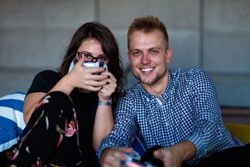 在家演奏计算机游戏的年轻微笑的夫妇 免版税库存图片