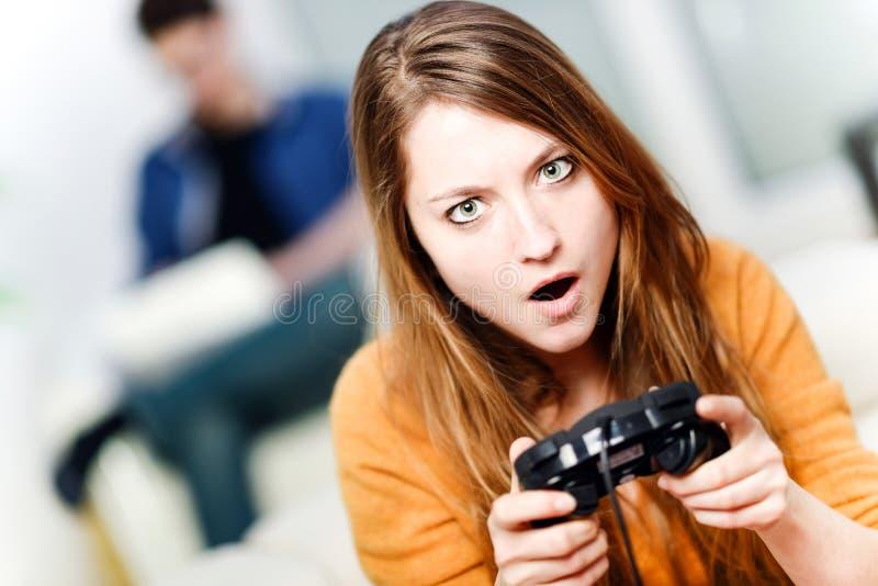 在家演奏计算机游戏的美丽的妇女画象 免版税库存图片