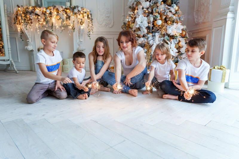 在家演奏闪烁发光物的母亲和五个孩子在圣诞树附近 图库摄影