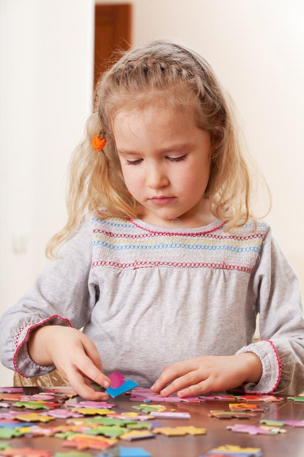 在家演奏难题的女孩 免版税库存图片