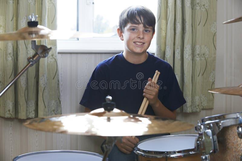 在家演奏鼓成套工具的男孩 库存图片