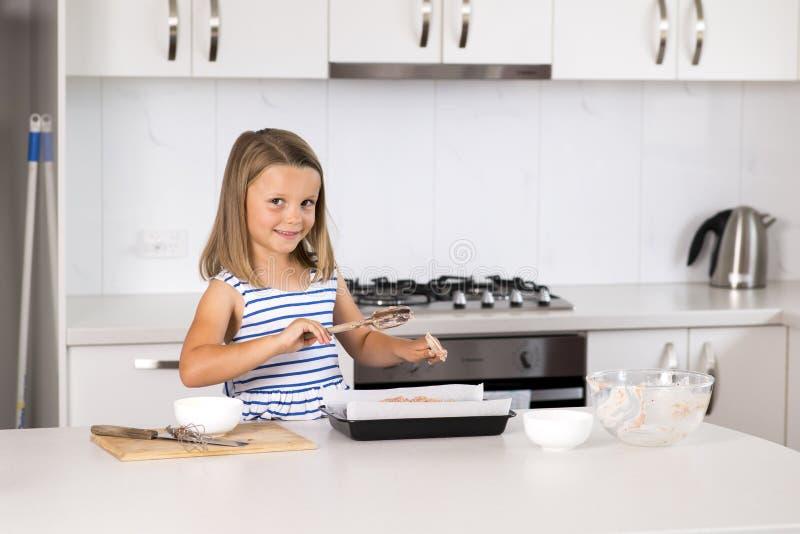 在家烹调和烘烤厨房的年轻美好和可爱的女孩6或7岁准备chocholate蛋糕微笑愉快和 免版税库存照片