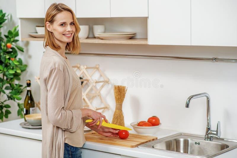 在家烹调晚餐的快乐的妇女 图库摄影