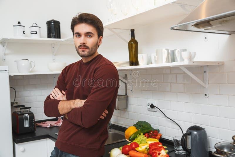 在家烹调浪漫晚餐的年轻人看严肃的照相机 图库摄影