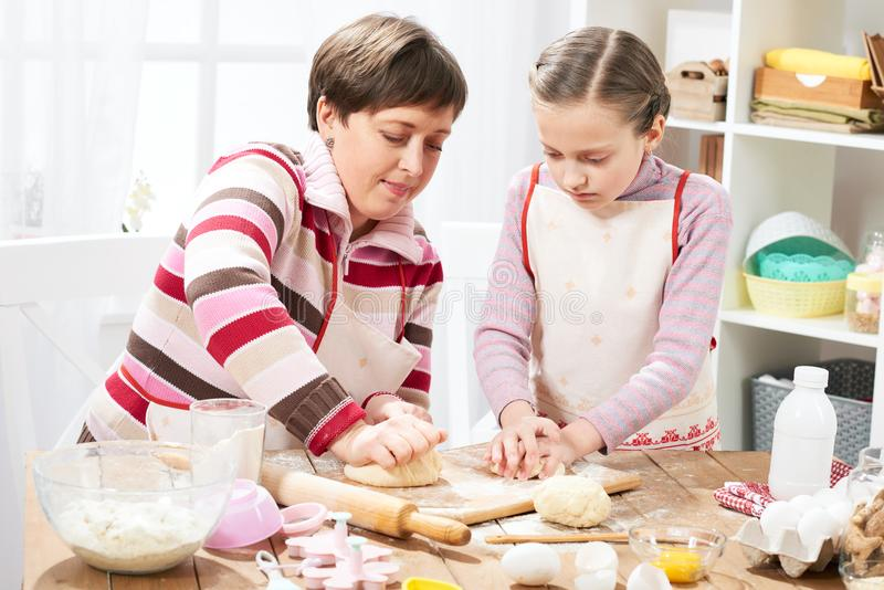 在家烹调的母亲和的女儿,做小圆面包的面团 免版税库存照片