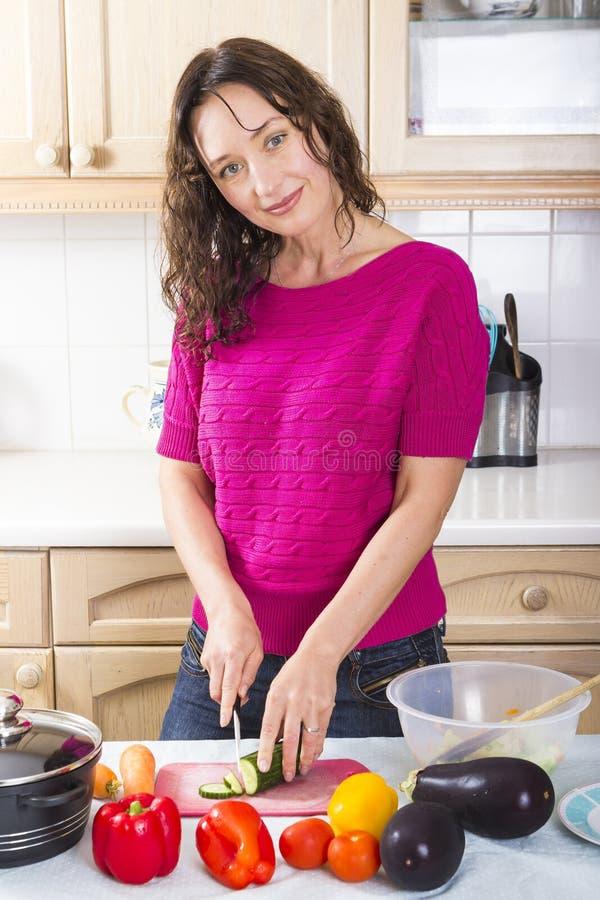 在家烹调菜的年轻浅黑肤色的男人 免版税库存图片