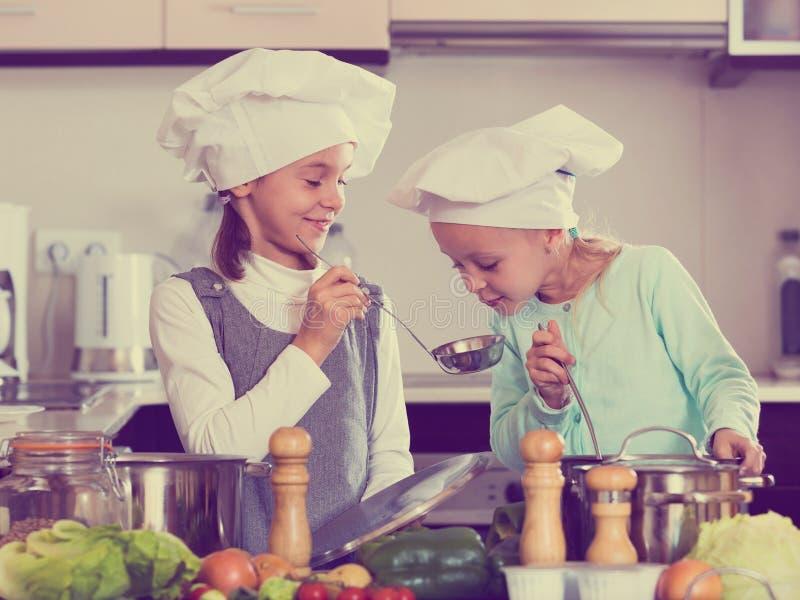在家烹调蔬菜汤厨房的两个微笑的女孩 图库摄影