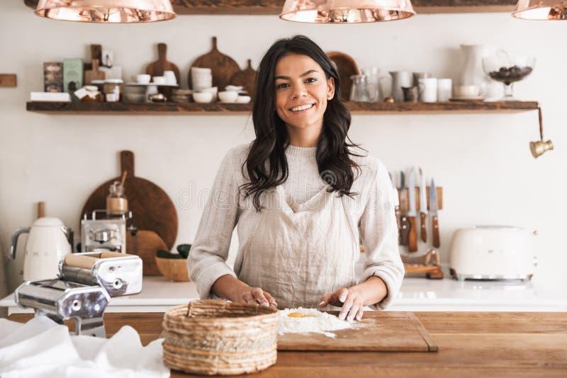 在家烹调酥皮点心用面粉和鸡蛋的微笑的妇女画象在厨房里 免版税库存图片