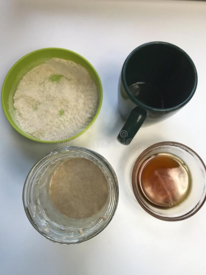 在家烹调面包发酵母 在桌上是成份 面粉、蜂蜜和水 免版税库存照片