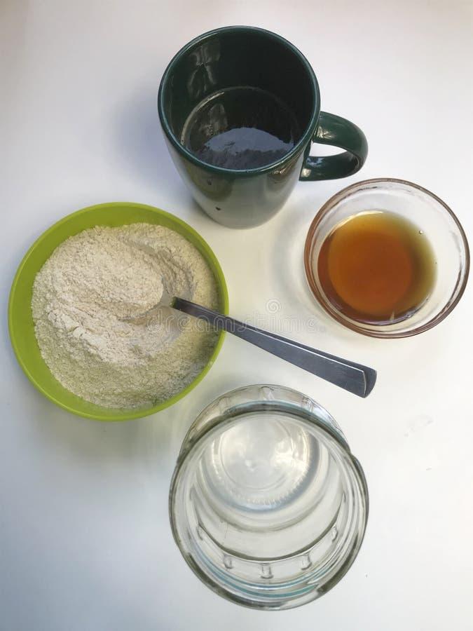 在家烹调面包发酵母 在桌上是成份 面粉、蜂蜜和水 免版税库存图片