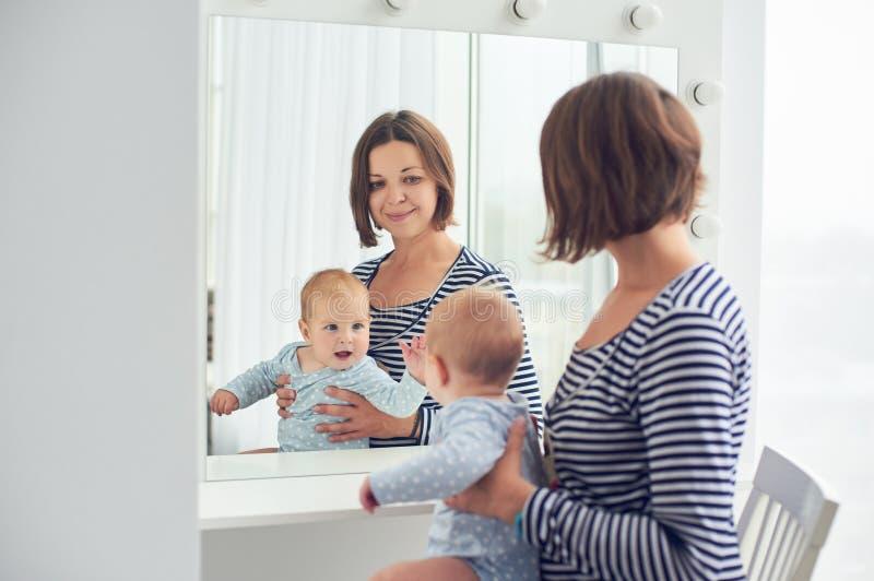 在家照顾与8个月在镜子的婴孩神色 免版税库存照片