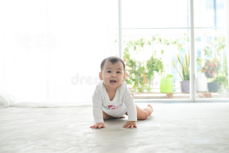 在家爬行在地板上的小俏丽的女婴 库存照片