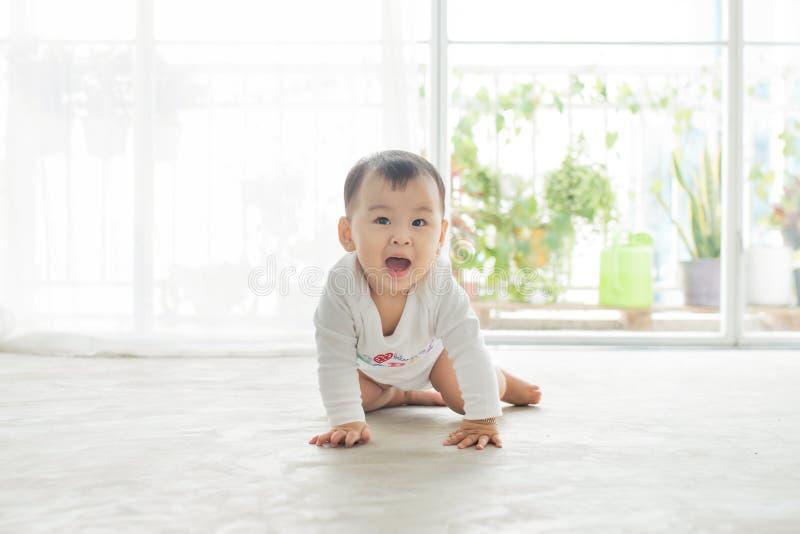 在家爬行在地板上的小俏丽的女婴 图库摄影