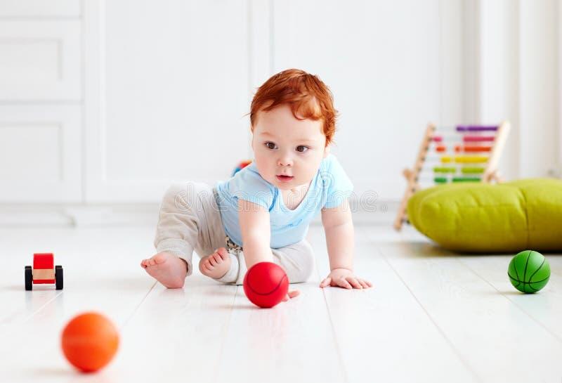 在家爬行在地板上的逗人喜爱的婴儿婴孩,使用与五颜六色的球 图库摄影