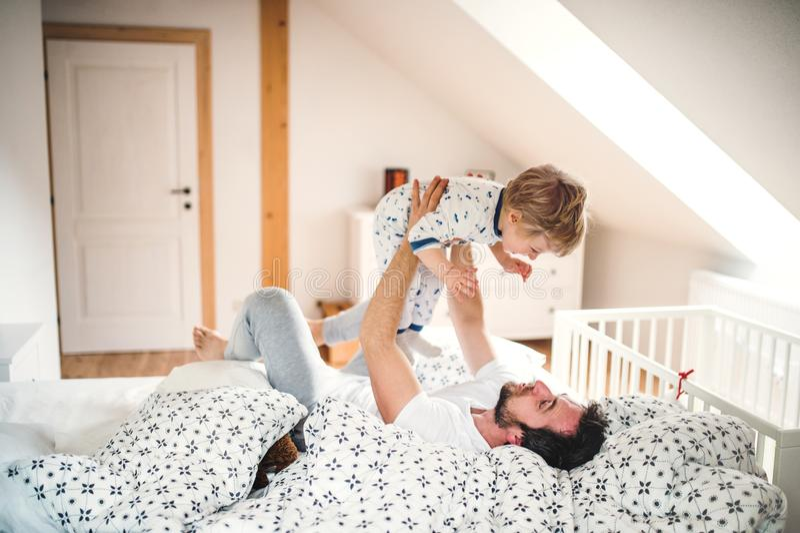 在家生与小孩男孩获得乐趣在卧室在上床时间 图库摄影