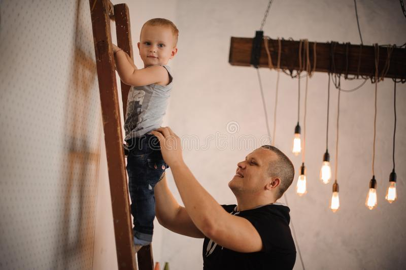 在家生帮助他的爬上梯子的小儿子 图库摄影