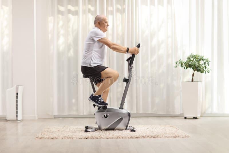 在家用固定自行车锻炼的成熟男人 库存照片