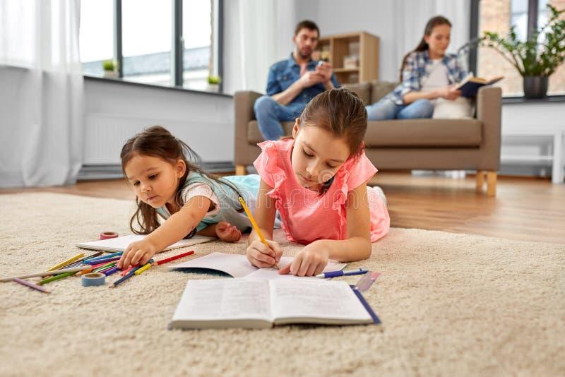 在家画和做家庭作业的愉快的姐妹 库存照片
