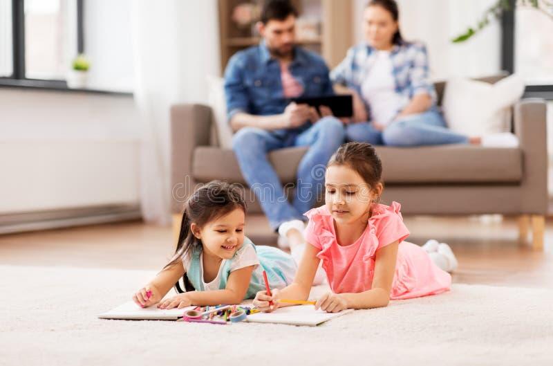 在家画在写生簿的愉快的姐妹 免版税库存照片