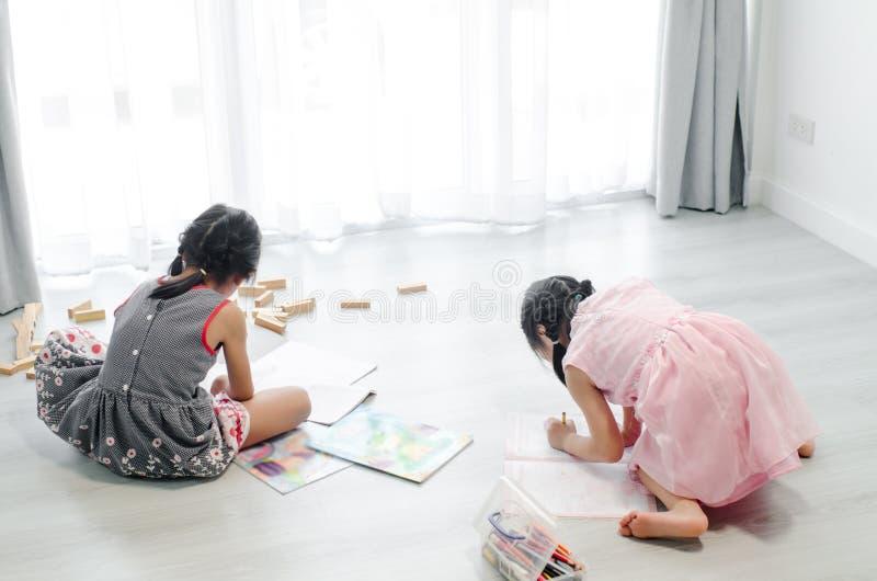 在家画在地板上的女孩图片 免版税图库摄影