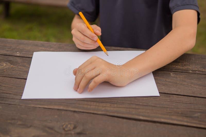 在家画逗人喜爱的小男孩 r 在幼儿园的创造性的孩子绘画 发展和教育概念 Happ 库存图片