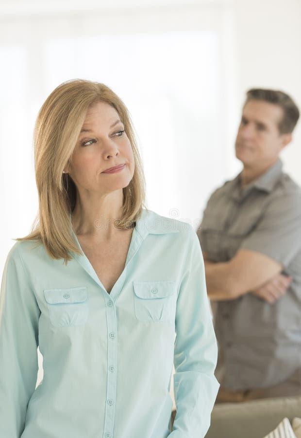 在家看与人的恼怒的妇女在背景中 库存图片