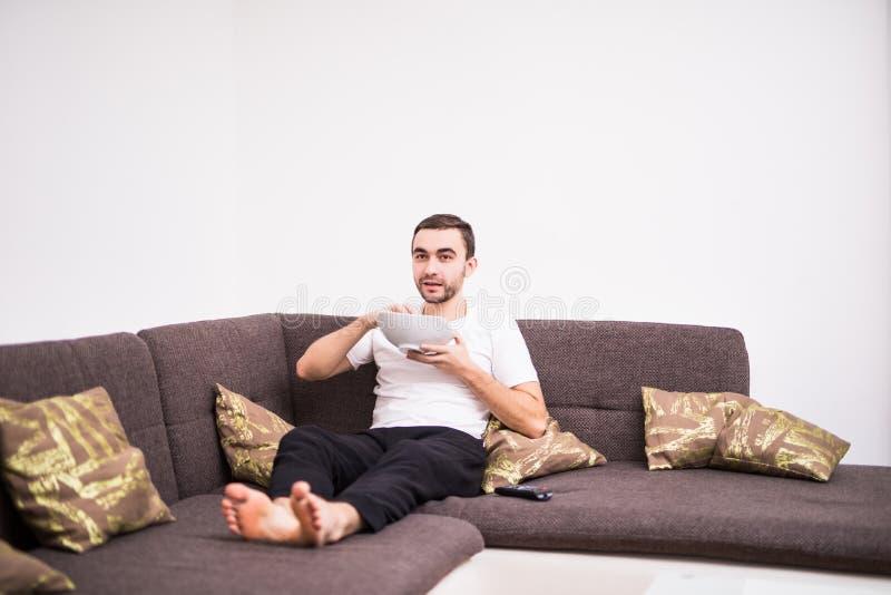 在家看在一个沙发的年轻英俊的人电视在公寓 库存照片