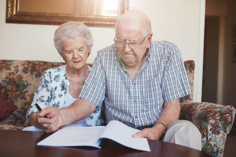 在家看在文件的退休的夫妇 免版税库存照片