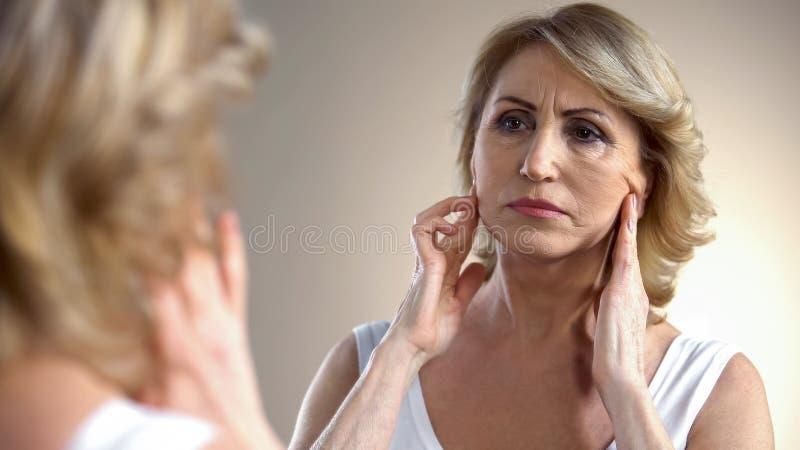 在家看在镜子的不快乐的年迈的妇女,接触面孔,变老的过程 免版税库存图片