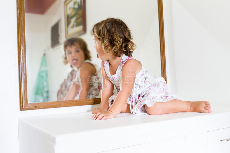 在家看她自己的漂亮的孩子女孩在镜子 免版税库存照片