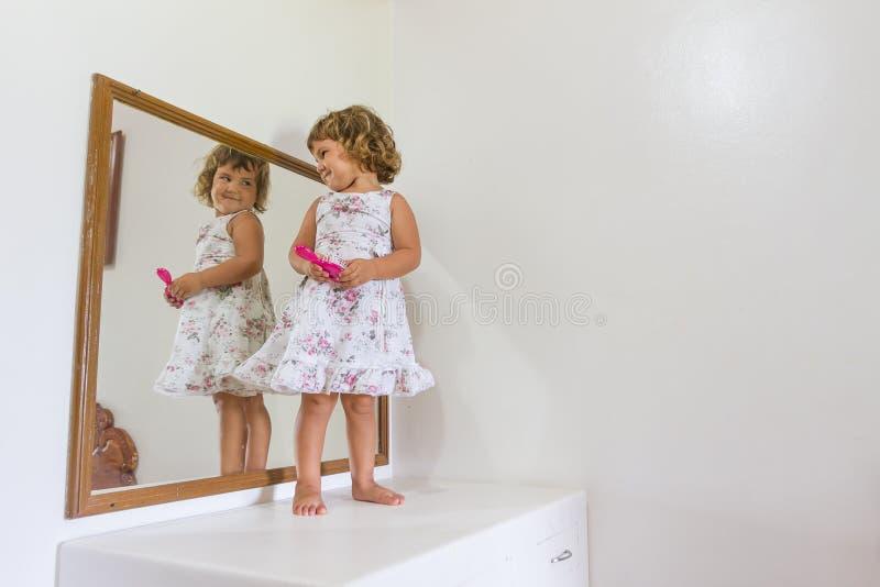 在家看她自己的漂亮的孩子女孩在镜子 免版税库存图片